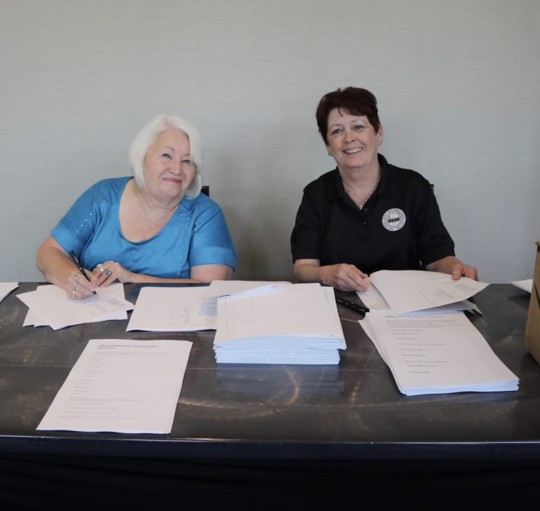 Two women volunteers smile from behind piles of voting ballots.