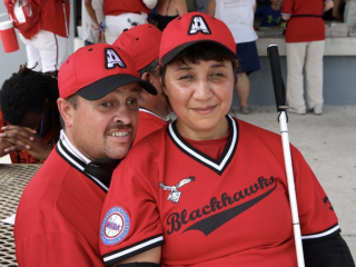 A couple of Austin Blackhawks smile for the camera while sitting in the concession area.