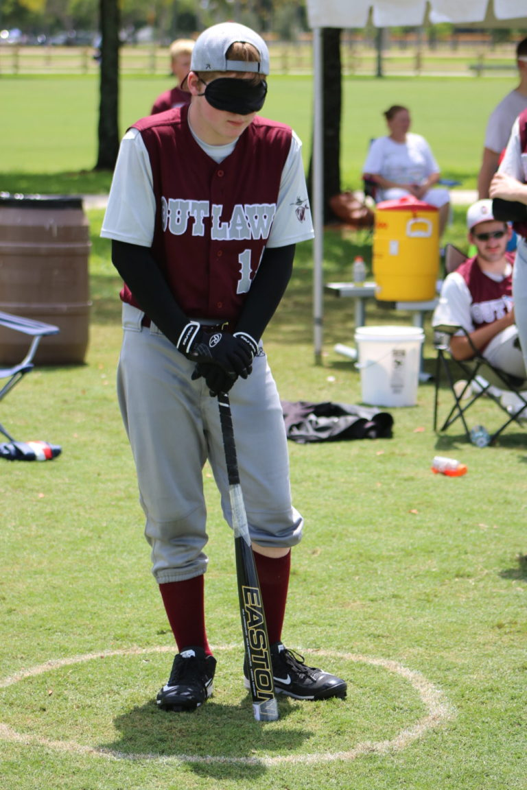 A BCS Outlaw player leans on his bat while waiting in the batting circle.