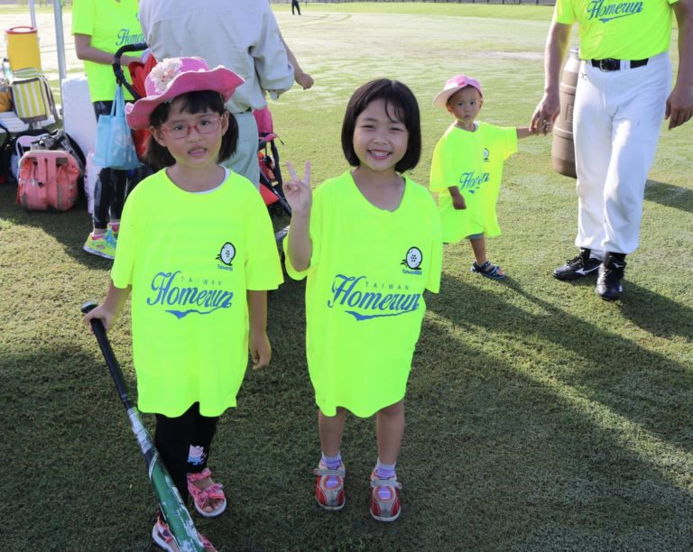 Two young girls dressed in Taiwan Homerun shirts pose for the camera.