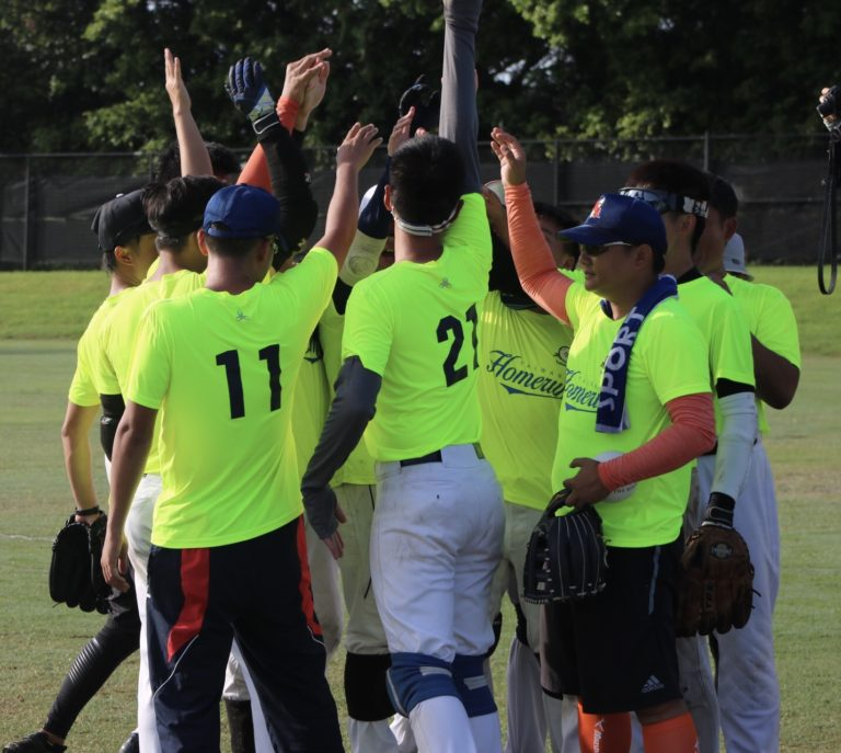 Taiwan Homerun huddle on the field with hands in the air.
