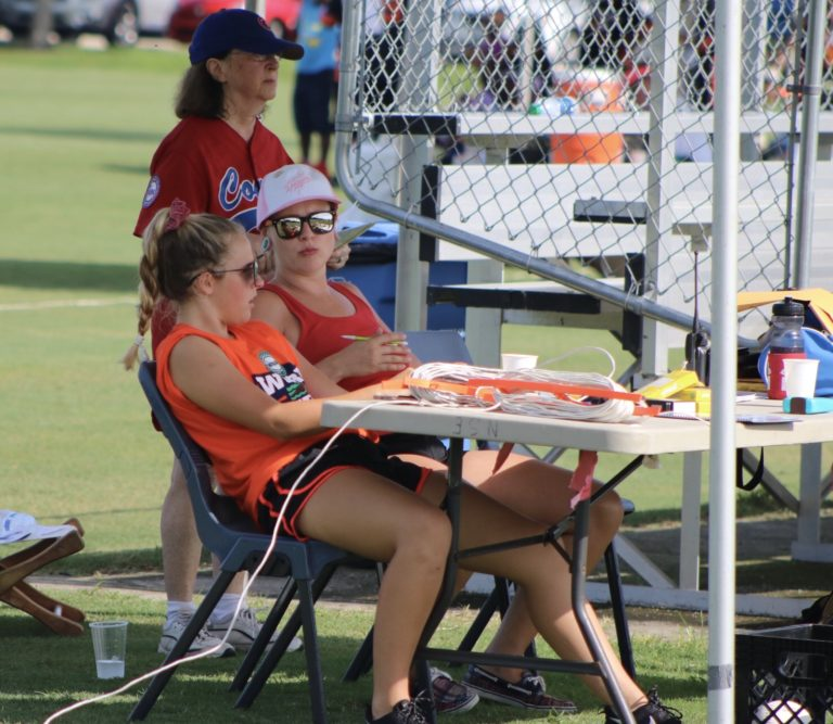 The base operator and scorekeeper focus on the game from behind a table.