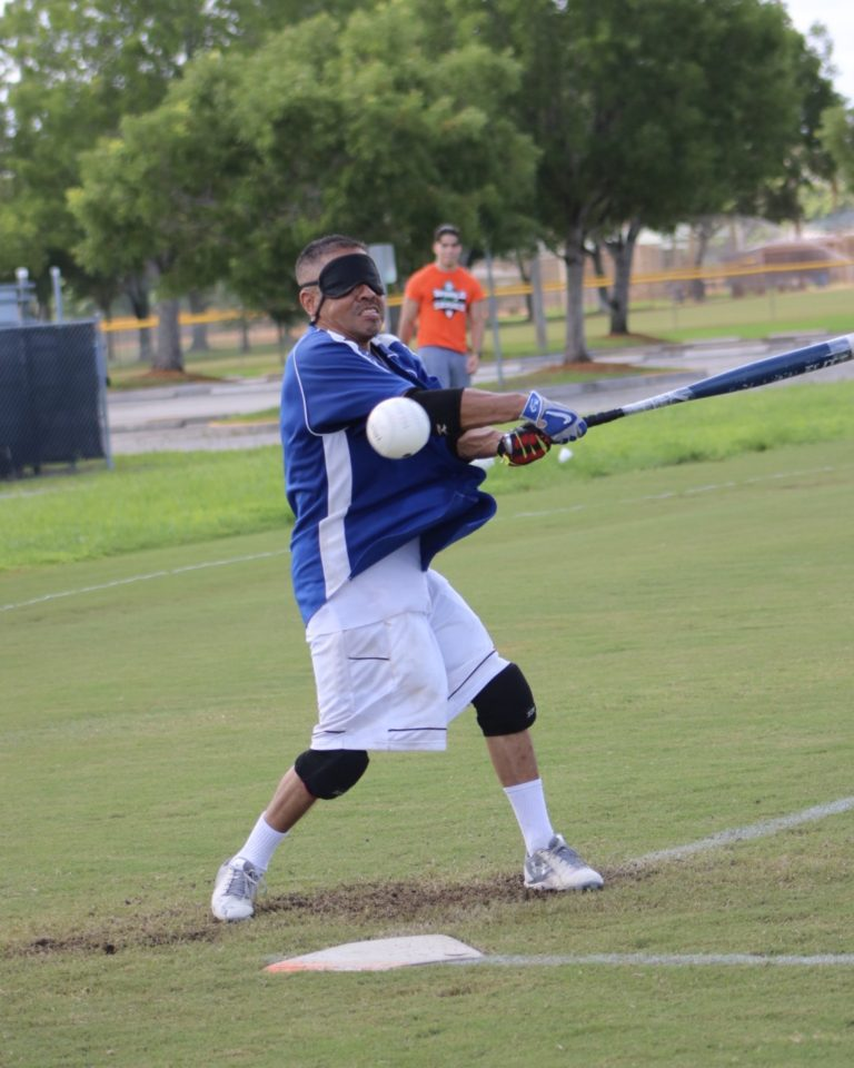 A player dressed in blue swings the bat as a ball hurdles towards him.