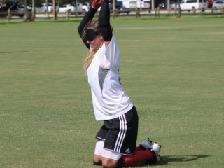 A blindfolded player rests on her knees while lifting the ball over her head with both hands.