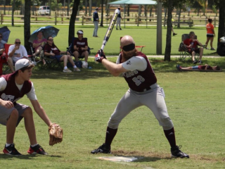 The BCS Outlaws' #23 in batting stance while the catcher readies himself.