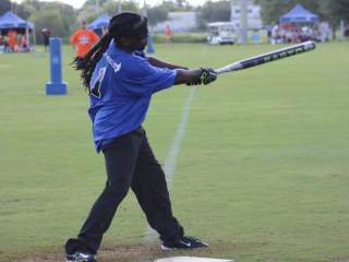 A player dressed in blue swings the bat.