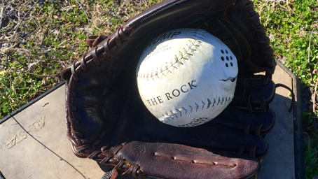 A close-up view of a beep ball resting in a pitcher's mit on home plate.