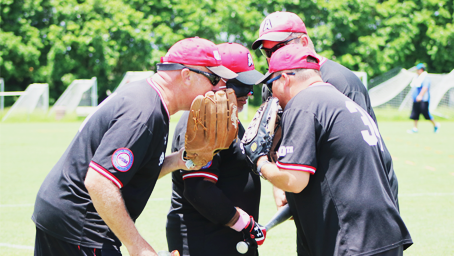 A few players huddle around their pitcher, who covers his mouth with his mit.