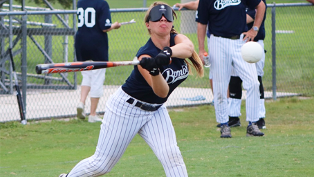 A player readies her swing as a ball heads toward home plate.