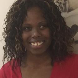 A close-up of Kalari wearing a red shirt and smiling.